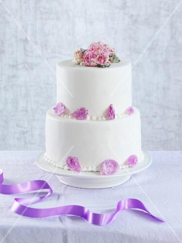 Zweistöckige Hochzeitstorte  Zweistöckige Hochzeitstorte mit kan rten Blumen – Bild