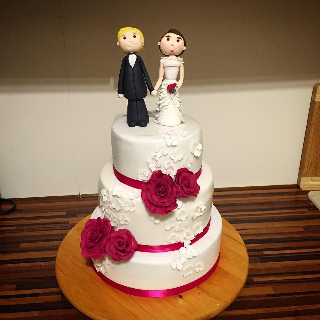 Hochzeitstorte Brautpaar  Eine Hochzeitstorte in weiß und fuchsia mit Brautpaar
